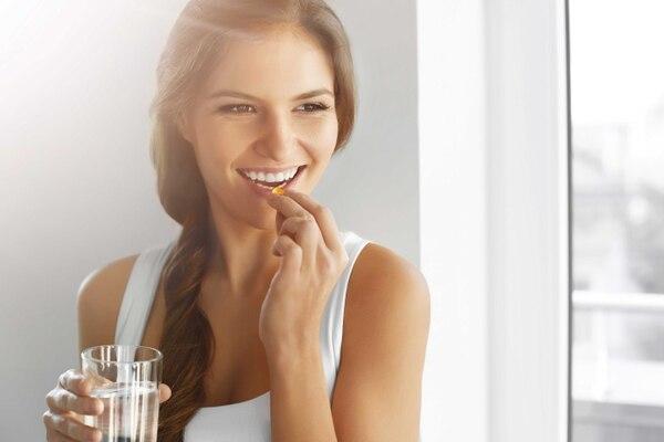 Mujer tomando una pastillita