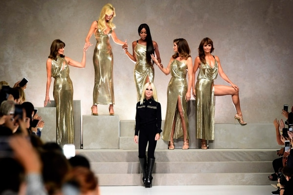 Top models (from left) Carla Bruni, Claudia Schiffer, Naomi Campbell, Cindy Crawford and Helena Christensen pose with Italian designer Donatella Versace (C) at the end of the show for fashion house Versace during the Women's Spring/Summer 2018 fashion shows in Milan, on September 22, 2017. / AFP PHOTO / Miguel MEDINA