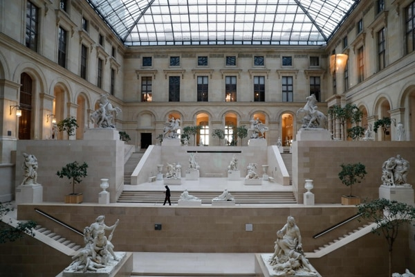 (FILES) In this file photo taken on March 13, 2020 an employee walks in the Cour Marly at the Musee du Louvre in Paris, undefinitely closed to the public amid concerns on the COVID-19 outbreak, caused by the novel coronavirus. - Museums and monuments in France will reopen from June 2, 2020, as part of the second phase of the easing of lockdown measures announced by the French Prime Minister on May 28, 2020 amid the COVID-19 (novel coronavirus) pandemic. (Photo by Thomas SAMSON / AFP)