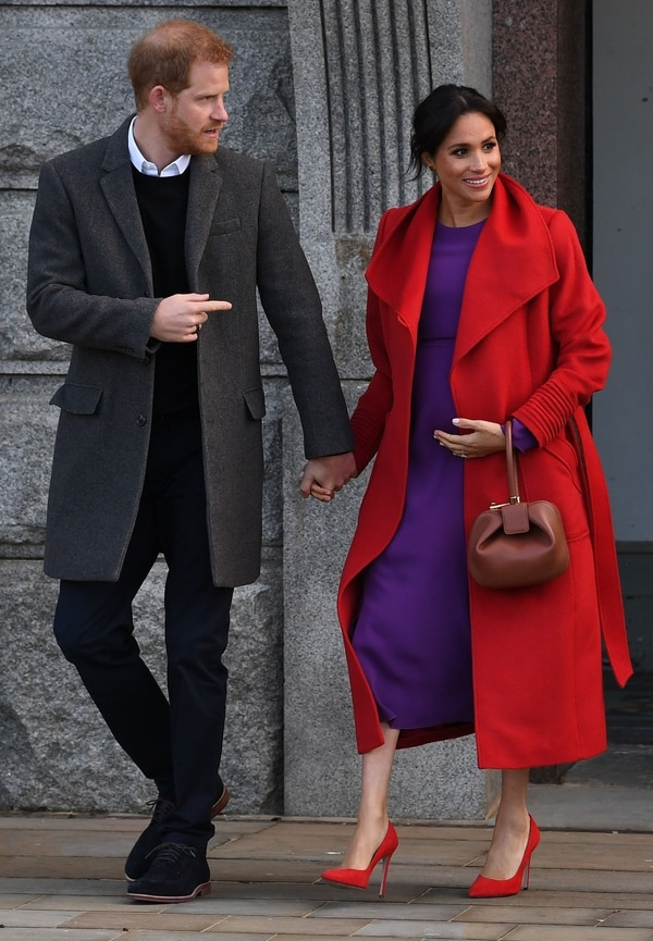 Britain's Prince Harry, Duke of Sussex (L) and his wife Meghan, Duchess of Sussex react during their visit to Birkenhead, northwest England on January 14, 2019. (Photo by Paul ELLIS / AFP)